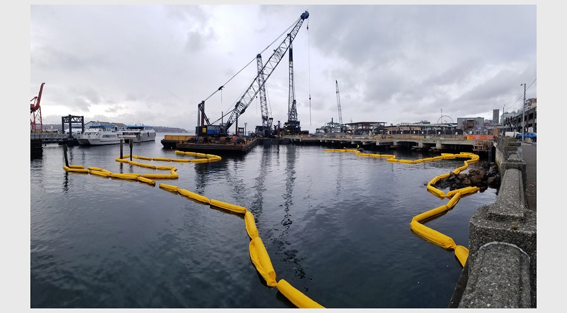 Photo of long yellow floats that mark the periphery of the marine habitat containment boom