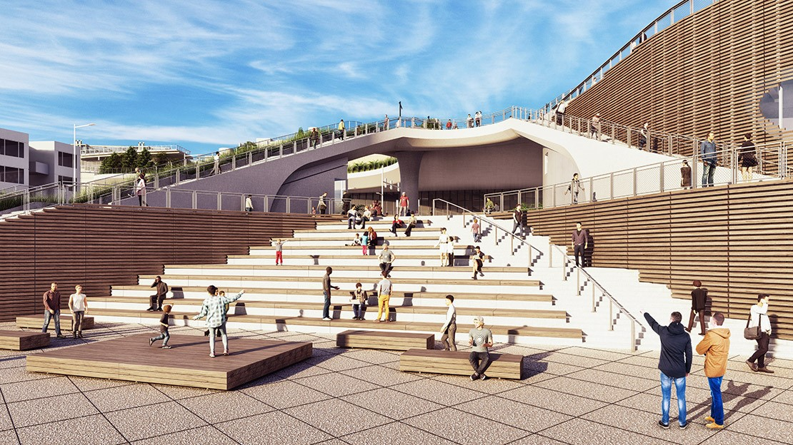 People congregate on steps that will double as an amphitheater. Small platforms with people on them sit at the bottom of the steps.