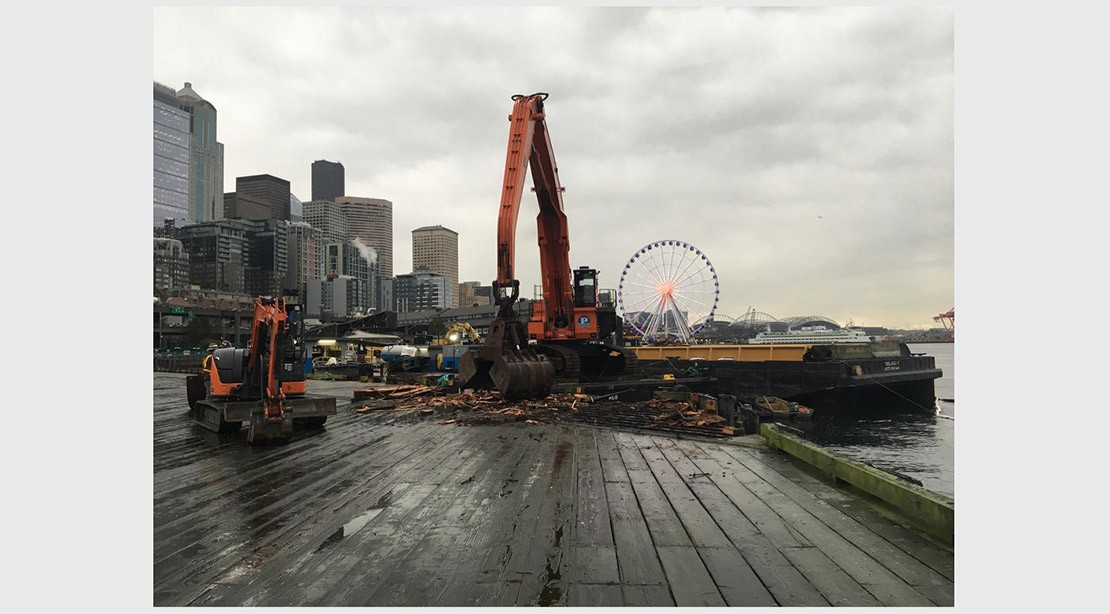 Photo of excavator removing timber decking on the old pier.