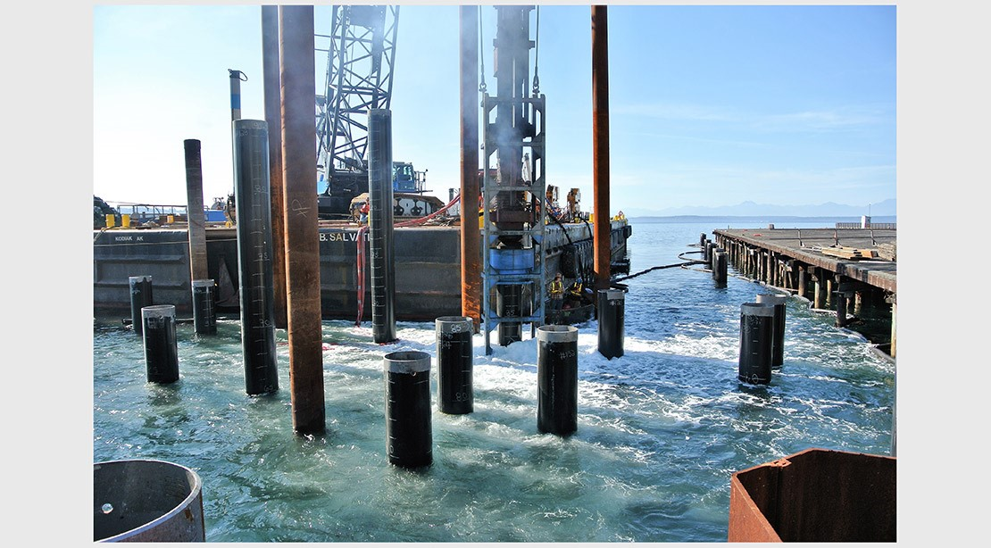 Photo of an orange vibratory pile extractor removing old wooden piles.