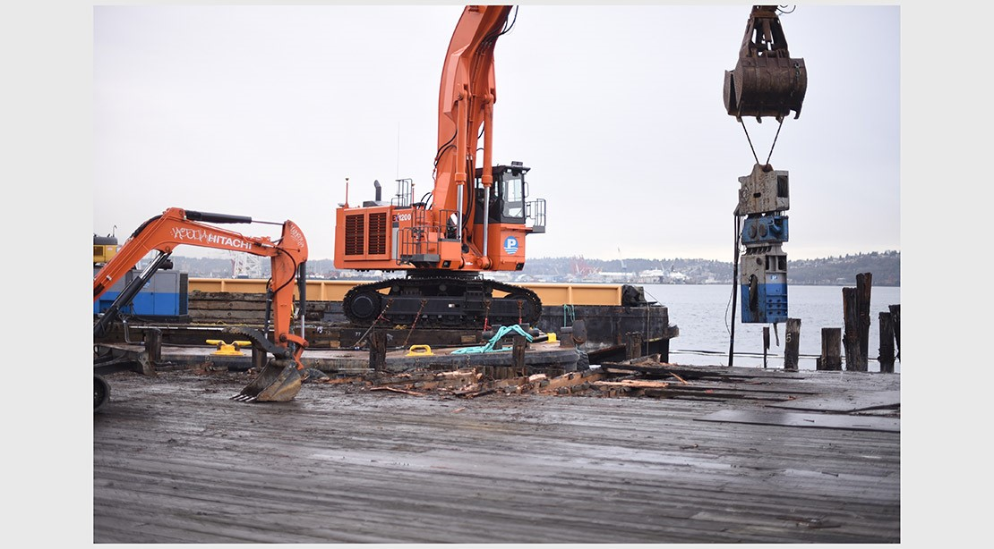 Photo of a square barge with a vibratory pile driver on-top installing new steel piles.