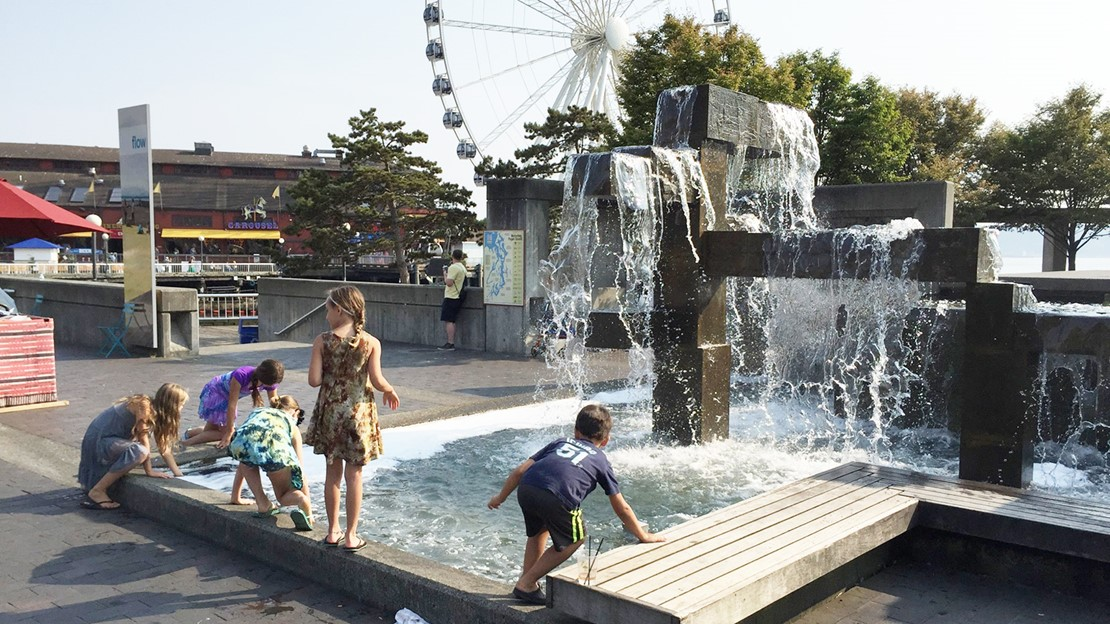 Children splashing and playing in a large fountain in a park on the waterfront, with a Ferris Wheel behind them