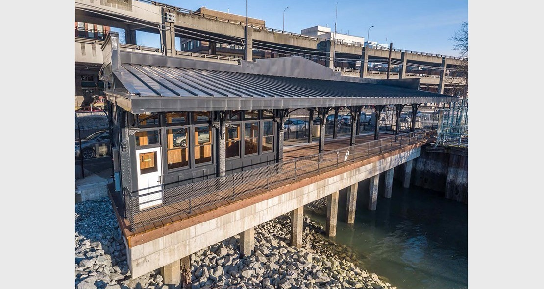 Photo of the reinstalled Washington Street Boat Landing Pergola, an outdoor structure consisting of columns that support a roofing grid of beams and rafters that is located by the water at the end of South Washington Street