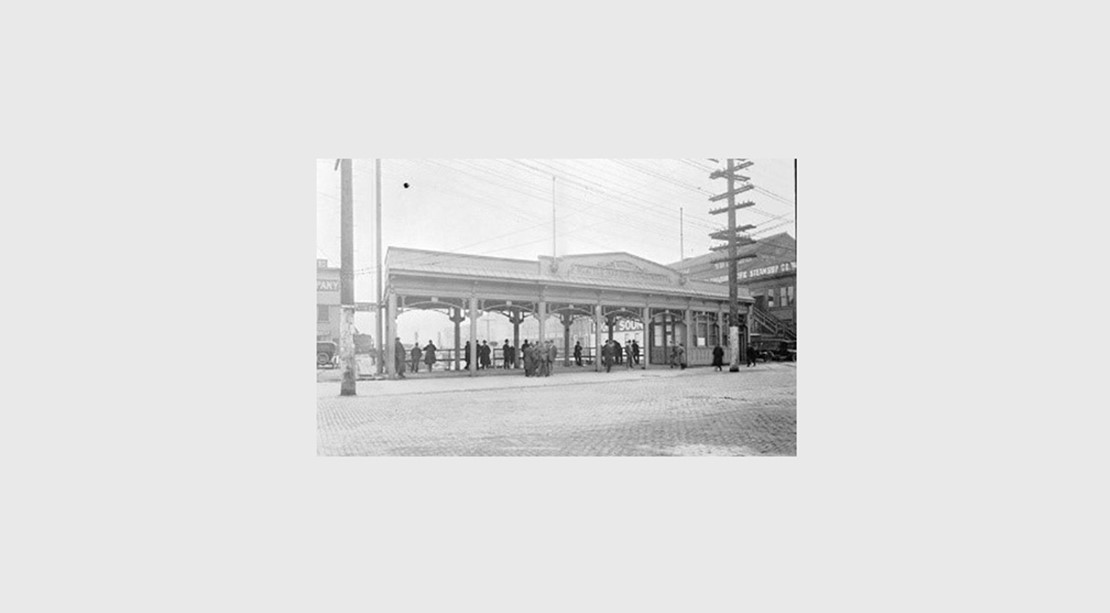 A historic black and white photo of a pergola on the waterfront with people sheltering under it.