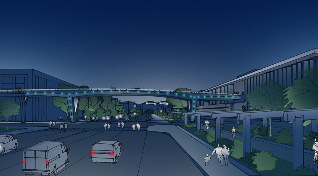 A rendering of vehicles driving under a pedestrian bridge that is lit up at night.