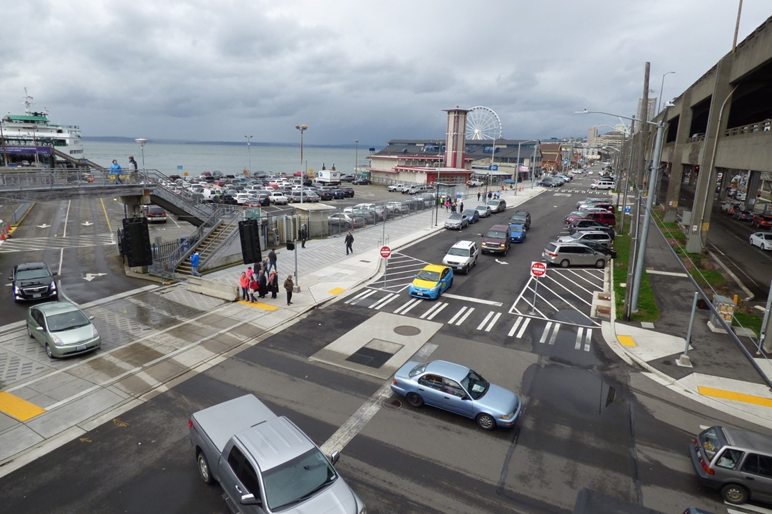 Photo shows vehicles exiting from a ferry to Alaskan Way South, a road that has one lane in each direction.