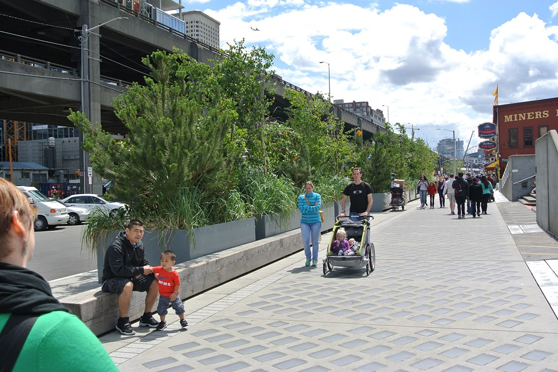 Photo shows people walking on a sidewalk with a light penetrating surface, including a family with a stroller next to green leafy plants.