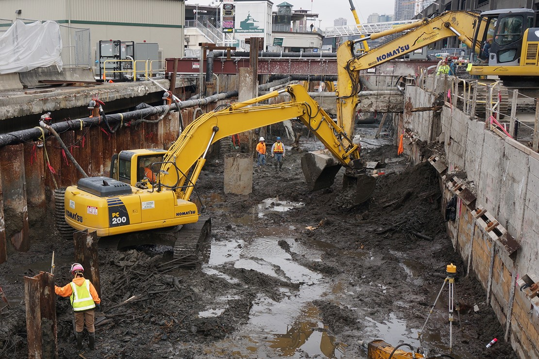 Photo shows excavator digging out muck to get to the old seawall's relieving platform.