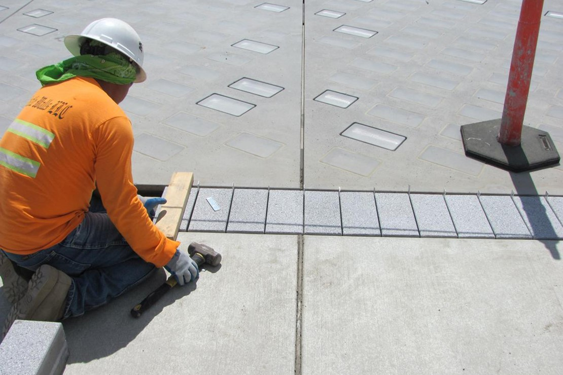 Photo shows a crew member measuring a piece of the sidewalk that will be restored.