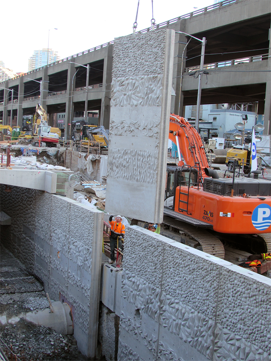 Photo shows one of the many concrete panels being placed on the seawall.