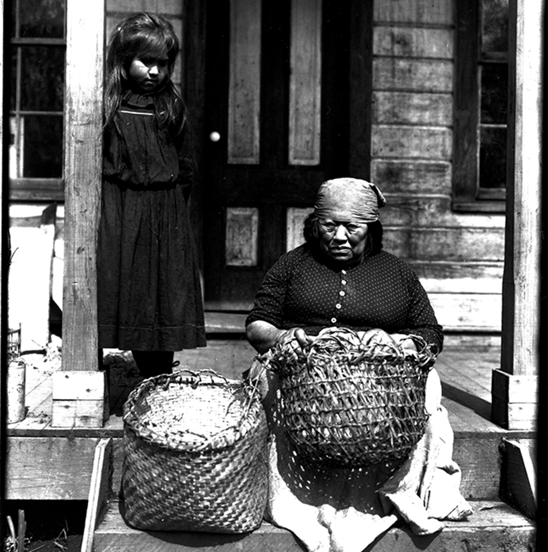 This weaver on the Skokomish Reservation in 1095 is seen with twilled cedar bark and cross-warp cedar root baskets. Photo by Asahel Curtis, courtesy of Washington State Historical Society